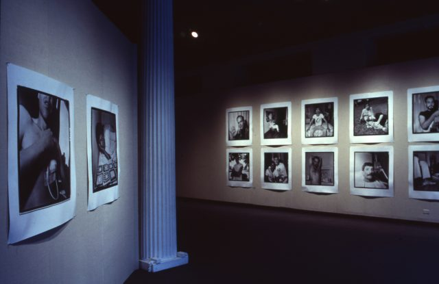 In a dark gallery, blown-up polaroid photographs are hung on the walls in rows. the polaroids are intimate portraits of people with AIDS, a variety of figures in casual poses in a variety of settings such as their homes, beds, and yards, sometimes posed with lovers or friends.